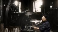 Eine Arbeiterin in einer Munitionsfabrik bei der Herstellung von Granaten. Foto von 1915.
