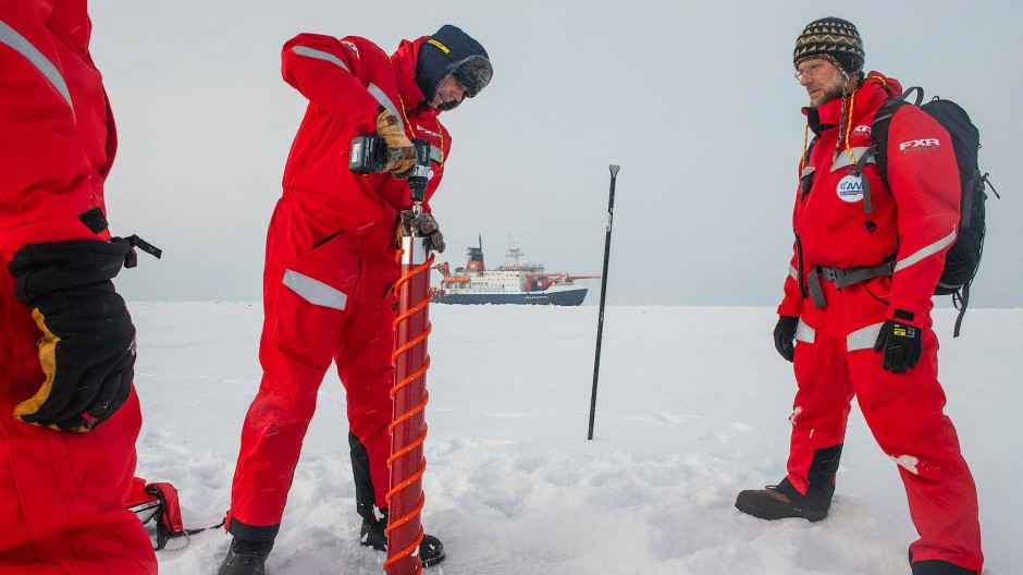 Die Wissenschaftler Gunnar Spreen (links) und Matthew Shupe untersuchen in Sichtweite des Forschungseisbrechers Polarstern eine Eisscholle.