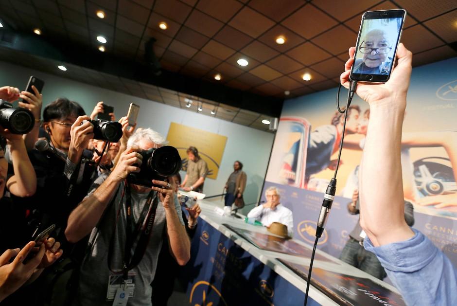Auftritt des Künstlers: Produzent Fabrice Aragno hält sein Handy hoch, als Jean-Luc Godard sich per Video-Schalte zu seinem Film äußert.