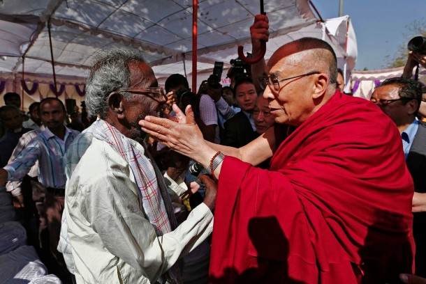 Exiled Tibetan spiritual leader, the Dalai Lama speaks with a leprosy-affected patient during his visit to a leprosy colony in New Delhi