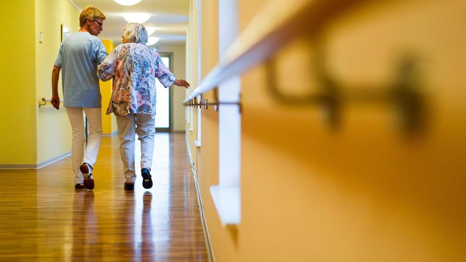 Eine Pflegekraft geht in einem Pflegeheim mit einer älteren Dame über einen Korridor.