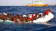 Gerettet: Flüchtlinge auf einem sinkenden Schlauchboot im Mittelmeer am Sonntag – sie wurden nach Lampedusa gebracht.