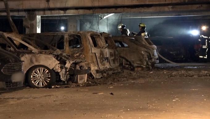 Feuerwehrleute löschen in der Nacht die letzten Feuer im Parkhaus am Münsteraner Flughafen.