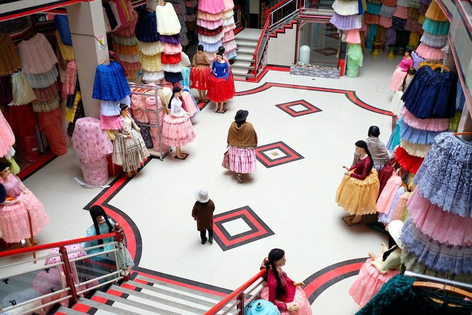 """Eine junge Frau läuft durch das gerade neu eröffnete Einkaufszentrum """"16 de Junio"""" in El Alto. Das Einkaufszentrum gehört zu den größten Märkten unter freiem Himmel und umfasst hunderte von Straßenständen und Geschäften."""