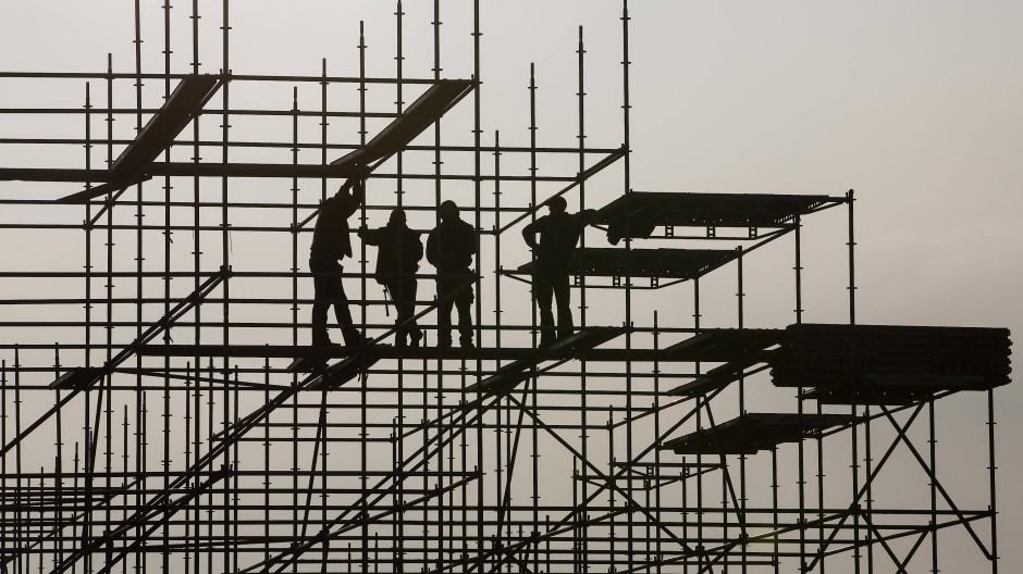 Gerüstbauer errichten auf einer Brückenbaustelle in der Hamburger Hafencity ein Gerüst.