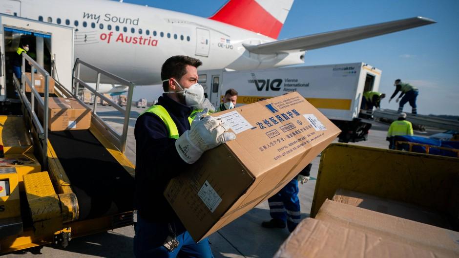 Arbeiter mit Mundschutz entladen am Flughafen Wien-Schwechat Schutzausrüstung aus einem Flugzeug der Fluggesellschaft Austrian Airlines, das aus China gelandet ist.
