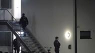 Polizisten betreten eine Flüchtlingsunterkunft in Sankt Augustin.