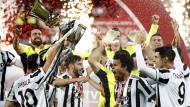 Juventus-Spieler feiern mit dem Siegerpokal ihren Sieg.