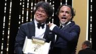 Der südkoreanische Regisseur Bong Joon-Ho (l) präsentiert seine Auszeichnung, der Präsident der Jury, Alejandro Gonzalez Inarritu, gratuliert.