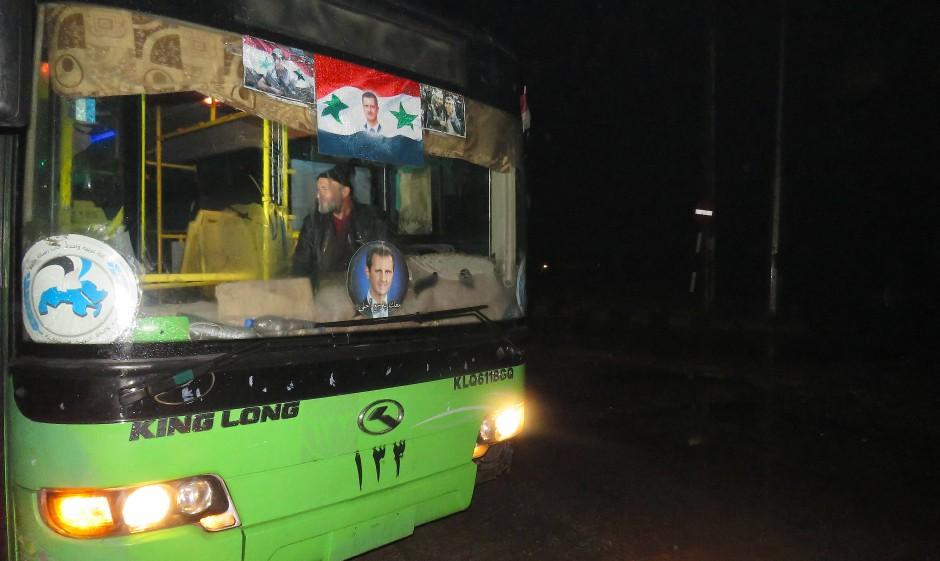 Einer der 20 Busse, mit denen die geschlagenen Rebellen aus Ost-Aleppo gebracht werden sollen – mit Assad-Bildchen in der Windschutzscheibe