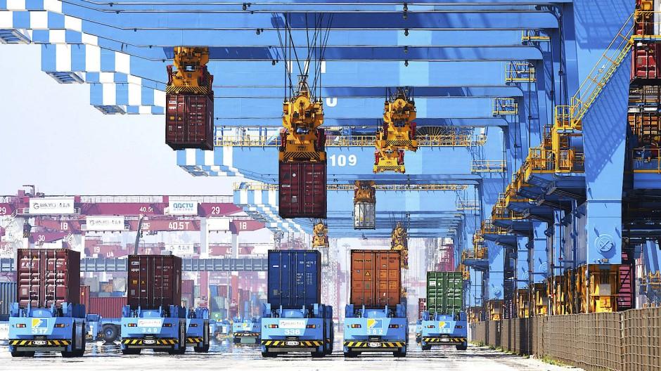 Portalkräne bewegen Container auf Transporter in einem Hafen in Qingdao in der ostchinesischen Provinz Shandong.