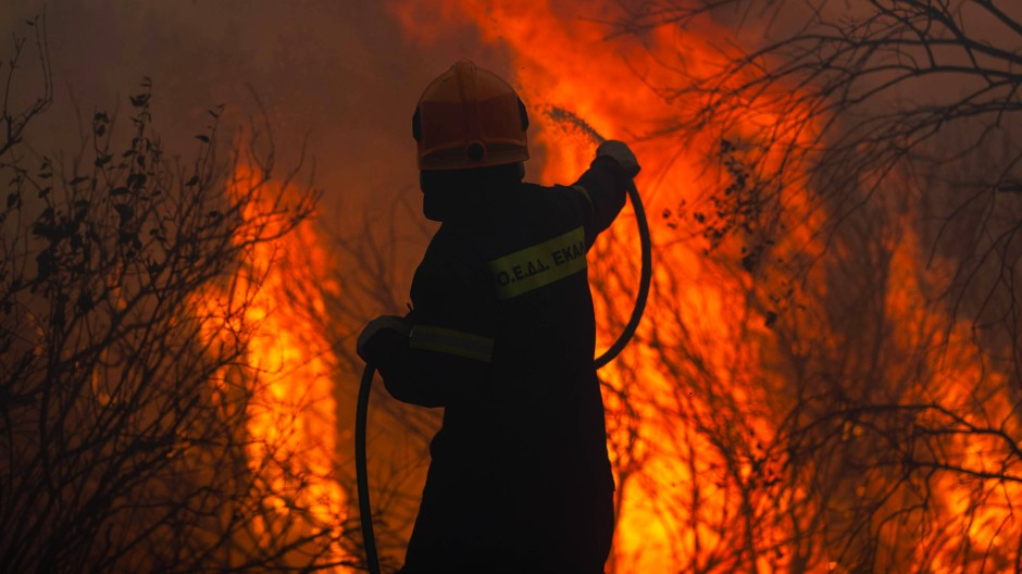 """""""Albtraumbrand"""": Ein Feuerwehrmann kämpft gegen einen Waldbrand in Varybobi."""