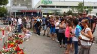 Passanten gedenken vor dem Olympia-Einkaufszentrum in München den Opfern des Amoklaufs.