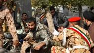 Soldaten und Zivilisten gehen vor den Schüssen in Deckung.