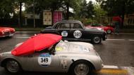 Mit Schirm und Charme: Porsche 550 Spyder und Mercedes-Benz 220 A von 1955 trotzen der himmlischen Attacke.