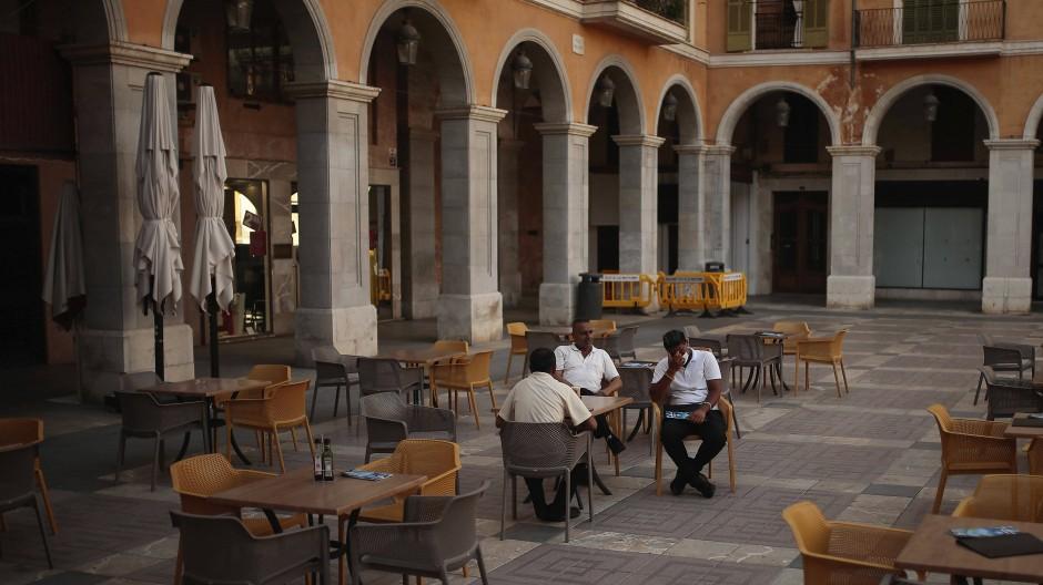 Die deutsche Reisewarnung trifft die Balearen hart: Drei Männer sitzen in Palma de Mallorca vor einem sonst leeren Lokal.