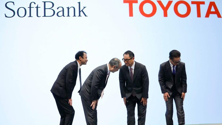 Keine Rosen – und dennoch ein fast künstlerisches Bild. Die Chefs von Softbank und Toyota begrüßen sich auf der Bühne.