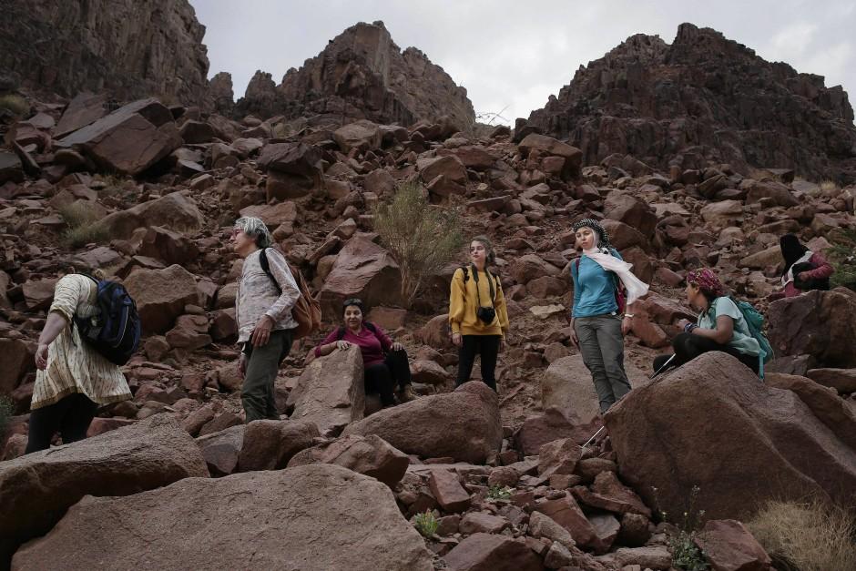 Eine Gruppe von Frauen allen Alters kämpft sich durch die schroffe Steinlandschaft in der Nähe von Wadi Sahw.