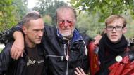Zwei Männer stützen den durch einen Wasserwerfer verletzten Dietrich Wagner (M) nach einer Demonstration gegen das Bahnprojekt Stuttgart 21.