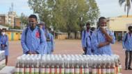 """Auf einem Schulhof in Madagaskar warten Schüler Ende April auf die Verteilung von """"Covid Organics""""."""
