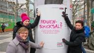 Frauenschicksal in Frankfurt: Frauendezernentin Rosemarie Heilig (r.), Gabriele Wenner (pinke Mütze), Leiterin des Frauenreferats und Linda Kagerbauer vom Frauenreferat präsentieren Plakate zum Internationalen Frauentag am 8. März.