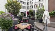 """Lauschiges Plätzchen: Auf dem Platz vor der Stadtbücherei sitzen die Gäste des """"Café Libretto"""" rund um den alten Tugendbrunnen."""