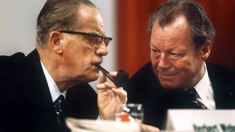 """Sein """"Zuchtmeister""""-Image wurde entmystifiziert: Der SPD-Fraktionsvorsitzende Herbert Wehner lauscht gespannt den Worten von Bundeskanzler Willy Brandt, während er seine Pfeife genießt."""