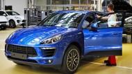 Porsche-Mitarbeiter mit einem fabrikneuen Porsche Macan-SUV in Leipzig.