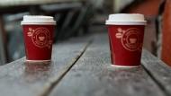 Zwei Kaffeebecher aus Pappe stehen auf einer Bank vor einem geschlossenen Café in Berlin.