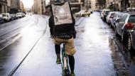 Ein kulinarisches Desaster auf zwei Rädern: Ein Fahrradkurier eines Lieferdienstes fährt über eine regennasse Straße in Berlin.