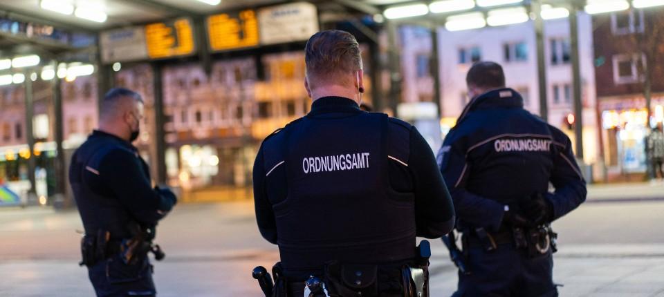 Drei Mitarbeiter des Ordnungsamts stehen auf dem Bahnhofsvorplatz in Hagen, wo bereits eine Ausgangssperre gilt.
