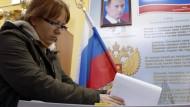 Und Präsident Putin schaut zu: Eine Wählerin in Moskau bei der Stimmabgabe in Moskau.