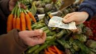 Auf einem Markt in Frankreich verkauft ein Händler Gemüse.