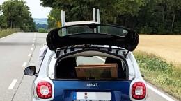 Mann transportiert Couchtisch auf Smart-Dach