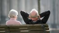 Senioren sitzen in Berlin auf einer Bank.