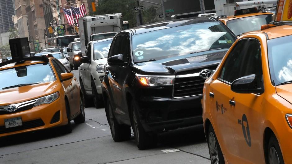 6th Avenue in New York City: Ein schwarzer Uber-Car steht zwischen Taxis im Stau.