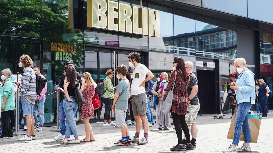 Berlin im Juni 2021: Menschen stehen mit Mund-Nasen-Schutz Schlange, um ein Geschäft zu betreten.