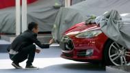Ein Mann fotografiert ein Tesla-Auto in Peking.