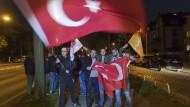 In Feierlaune: Unterstützer des türkischen Präsidenten Erdogan schwenken am Sonntagabend Fahnen vor dem türkischen Generalkonsulat.