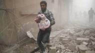 Angriff aus der Luft: In der Rebellenhochburg Douma östlich von Damaskus bringt ein Mann ein Baby in Sicherheit.
