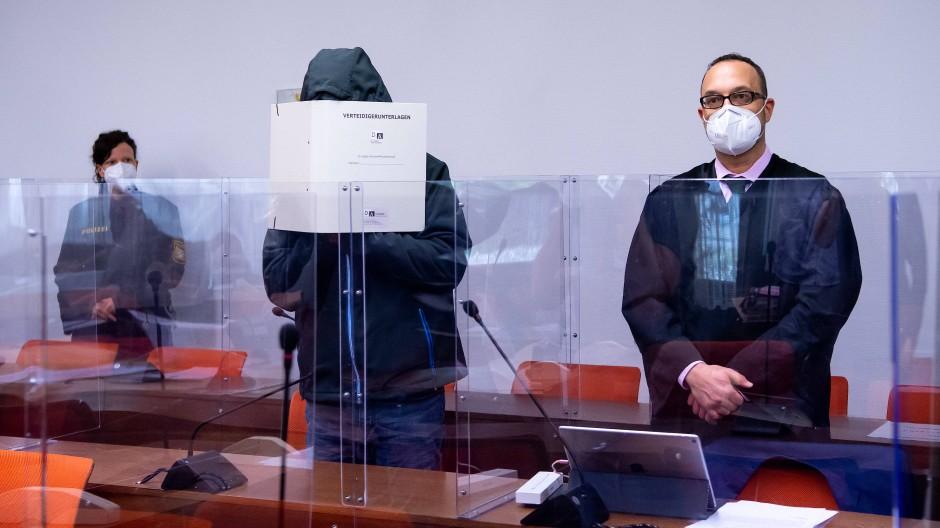 Mit übergezogener Kapuze und Aktendeckel vor dem Gesicht stellte sich der Angeklagte am Mittwoch den Fotografen.