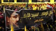 Hizbullah-Unterstützer halten bei einer Kundgebung im April in Beirut ein Banner mit dem Bild von Hizbullah-Führer Nasrallah hoch.