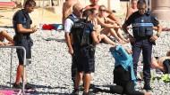 Aktion des Anstoßes: Vier Polizisten fordern eine Frau am Strand von Nizza auf, den Burkini abzulegen.