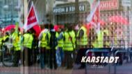 Streikende Mitarbeiter der Warenhauskette Karstadt spiegeln sich am 25.10.2013 in Hannover im Schaufenster einer Karstadt Filiale.