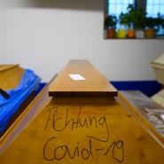 """""""Achtung Covid-19"""" steht auf einem Sarg mit einem Verstorbenen, der an oder mit dem Coronavirus gestorben ist."""
