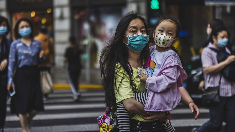 Familien und Werte im Wandel: Eine Frau trägt ihr Kind in Schanghai.