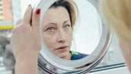 Eine Patientin begutachtet sich nach einer Augenbrauen-Transplantation im Spiegel.