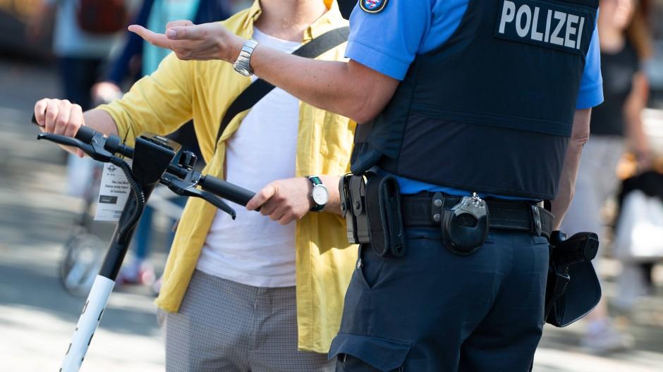 Ein Polizeibeamter hält bei einer Polizeikontrolle einen E-Scooter-Fahrer auf dem Platz vor der Alten Oper in Frankfurt an.