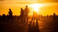 Menschen spazieren während des Sonnenuntergangs auf dem Tempelhofer Feld.