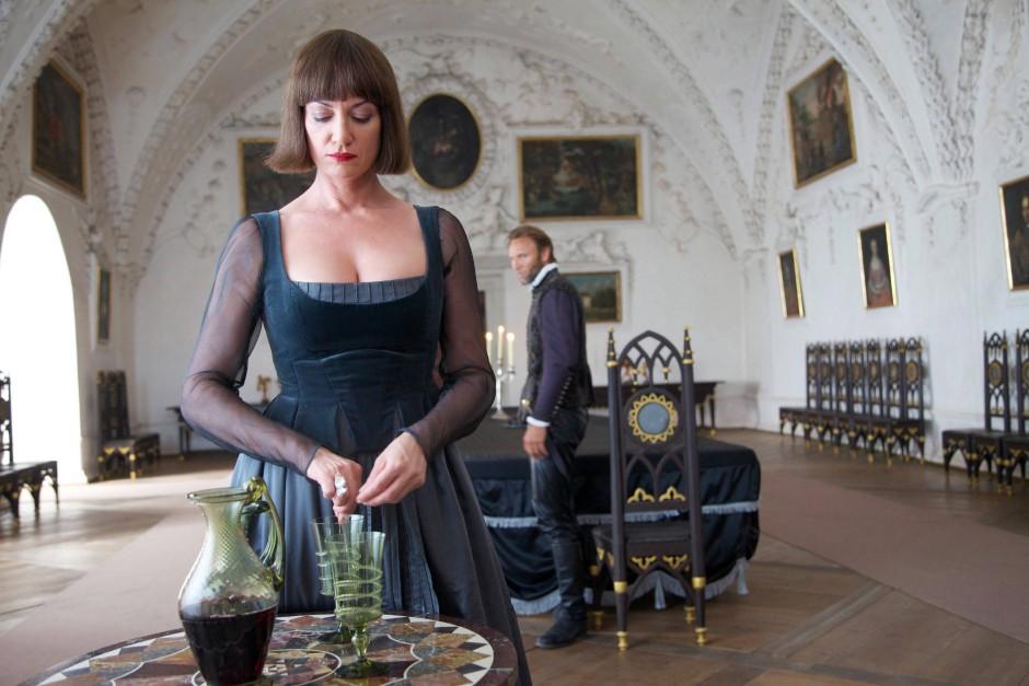 Die abgefeimte und machtwahnwitzige Adelheid von Walldorf (Natalia Wörner) füllt Gift in das Weinglas ihres Gatten August (Bernhard Bettermann)
